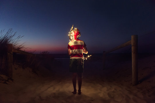 Boy carrying driftwood decorated with Christmas lights