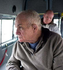 Two men with a disability seated on a bus