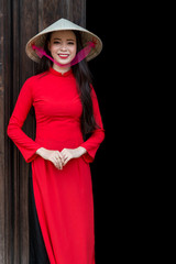 Vietnamese woman in red Ao Dai, traditional costume, and conical hat
