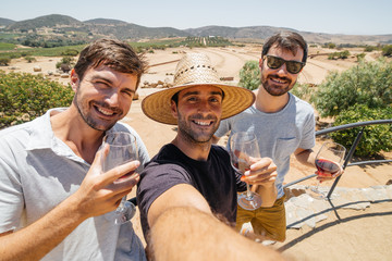 Group of friends sellfie enjoying wine tasting in a vineyard