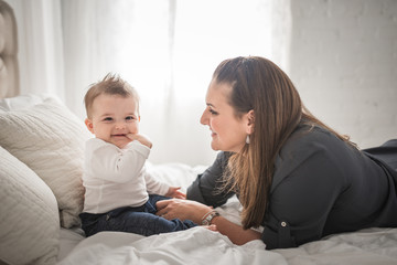 A MotherSmiles At Her Baby On A Bed