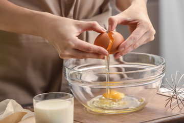 Female chef making dough in glass bowl on kitchen table