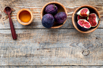 Fresh blue figs in bowl and honey on wooden background top view copyspace