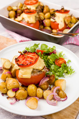 Oven baked tomatoes stuffed with minced meat, cheese and herbs. Served with new potatoes and salad. Casserole oven dish visible on white wooden background