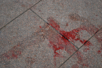 Blood left on a tile at the place of crime scene. Stain on old granite texture