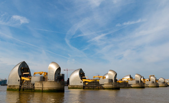 The metallic Thames Barrier gates and piers on a summers day with wispy clouds in the sky in Greenwich London.