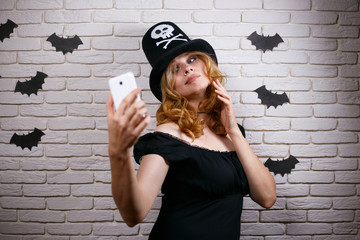 Young beautiful woman in Halloween hat taking a selfie.  Halloween, celebration, party concept