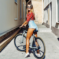 Outdoor summer portrait of attractive girl on fixed gear bike