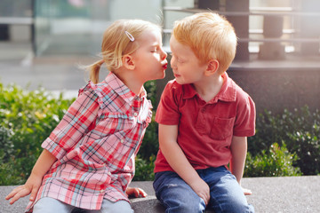 Group portrait of two white Caucasian cute adorable funny children toddlers sitting together kissing each other. Love friendship fun concept. Best friends forever.