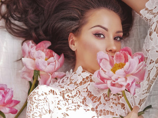 Beautiful young woman lies among peonies Fototapete