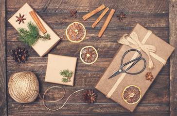 Set for Christmas gift wrapping. Presents wrapping inspirations. Gift box, ball of jute, cinnamon sticks, anise, orange slices, fer tree branches  and retro scissors on rustic wooden background.