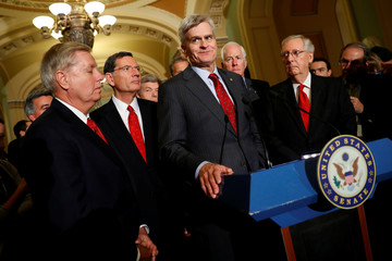 Sen. Bill Cassidy (R-LA), accompanied by (L-R) Sen. Lindsey Graham (R-SC), Sen. John Barrasso (R-WY), John Cornyn (R-TX), and Senate Majority Leader Mitch McConnell, speaks with reporters following the party luncheons on Capitol Hill in Washington