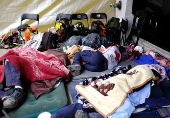 Members of rescue team and volunteers rest in front of a collapsed building, after an earthquake in Mexico City