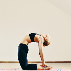 Young fit woman doing yoga indoors