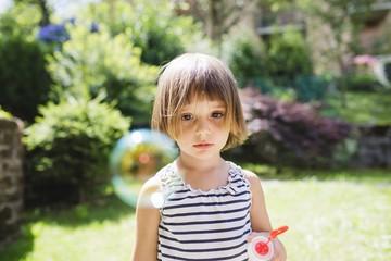 Cute little girl looking a soap bubble