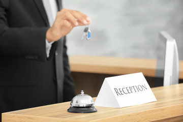 Reception sign with service bell and hotel receptionist on background