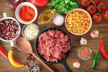 Composition with raw minced meat and chili con carne ingredients on wooden background
