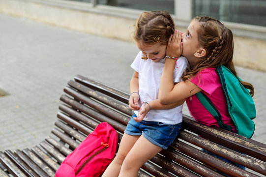 Older sister telling a secret to her younger sister
