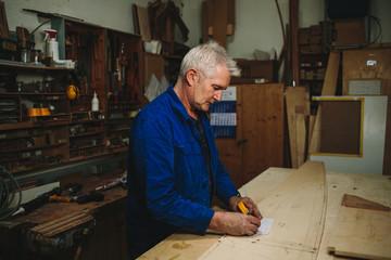 senior carpenter drawing a plan in his workshop