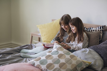 Sisters Lying on a Bed and Reading
