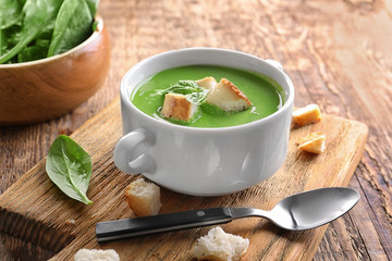 Tureen with delicious spinach soup on wooden table