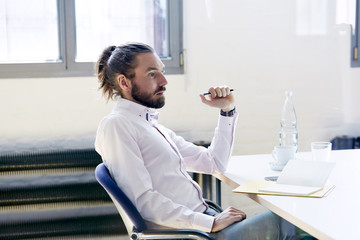 Thoughtful Mid Adult Businessman Sitting At Desk In Office