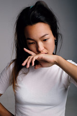 Asian black-haired woman with hand at lips looking down