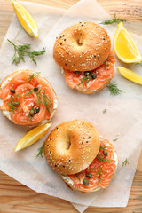 Tasty bagels with salmon on parchment