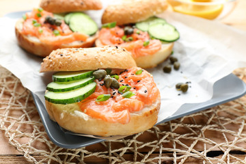 Tasty bagel with salmon on plate, closeup
