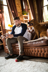 Man siiting on sofa playing video games, his dog sitting close to him. Young male at home with his staffordshire terrier