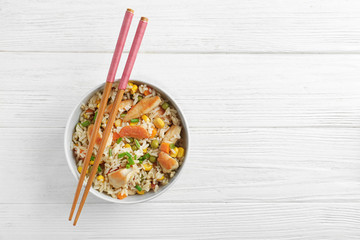 Bowl with brown rice, vegetables and chopsticks on wooden table