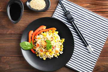 Plate with brown rice and vegetables on wooden table
