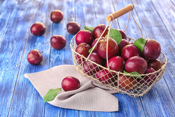 Metal basket and ripe plums on table