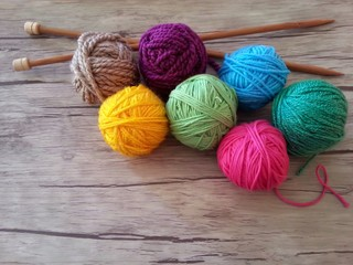 Multicolored yarn balls and wooden needles for knitting on wood background
