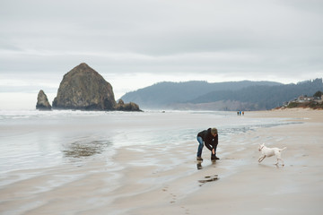 Young man playing with his dog near a huge rock formation on the Oregon coast.