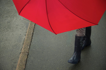 red umbrella held by someone on sidewalk