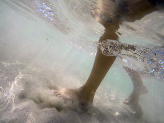 underwater image of girl feet walking on a sand calm beach on a sunny summer day