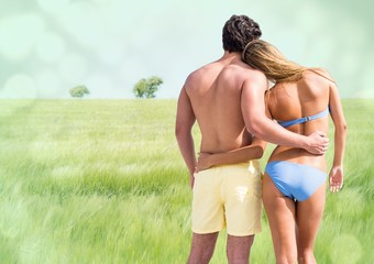 Back of couple in swimsuits against blurry meadow