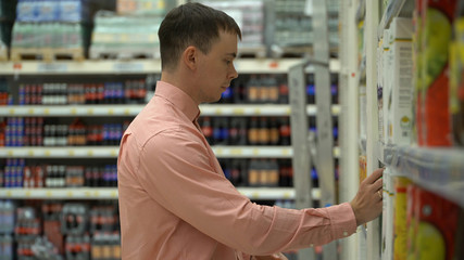 young guy buys juice in a store or supermarket.