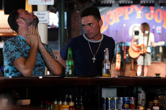 Men sit at the bar at a mostly empty Sloppy Joe's bar following Hurricane Irma in Key West, Florida