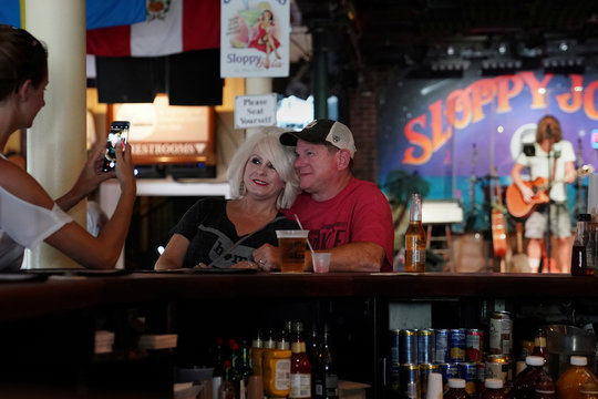 A couple poses for a photo at a mostly empty Sloppy Joe's bar following Hurricane Irma in Key West, Florida