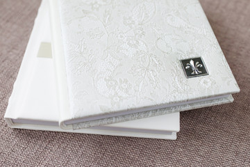 Photo books with a cover of genuine leather. White color with decorative stamping . Soft focus.