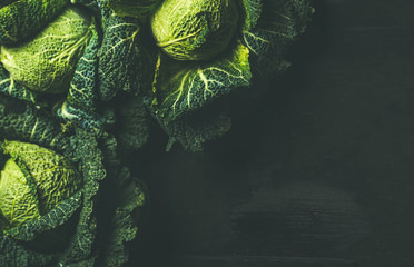 Raw fresh uncooked green cabbage over dark background, top view, selective focus, copy space