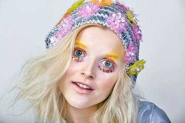 Young girl with colorfull makeup in sparkling hat