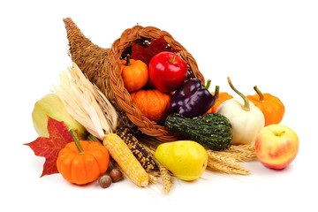 Thanksgiving cornucopia filled with fruit and vegetables isolated on a white background