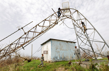 A radio station engineer removes needed equipment from a tower mangled by Hurricane Maria last week, as soldiers from the U.S. Army's Civil Authority Information Support Element assist below, on St. Croix, U.S. Virgin Islands