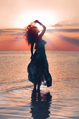Elegant woman on water. Sunset and silhouette