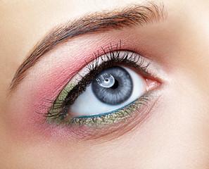 Closeup macro image of human woman eye with pink and green makeup