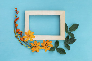 Wooden frame with fresh and dry yellow flower arrangement on blue background