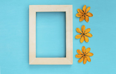 Wooden frame with yellow flower on blue background